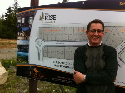 Jason Andrew stands in front of sign announcing The Rise at Crown Isle